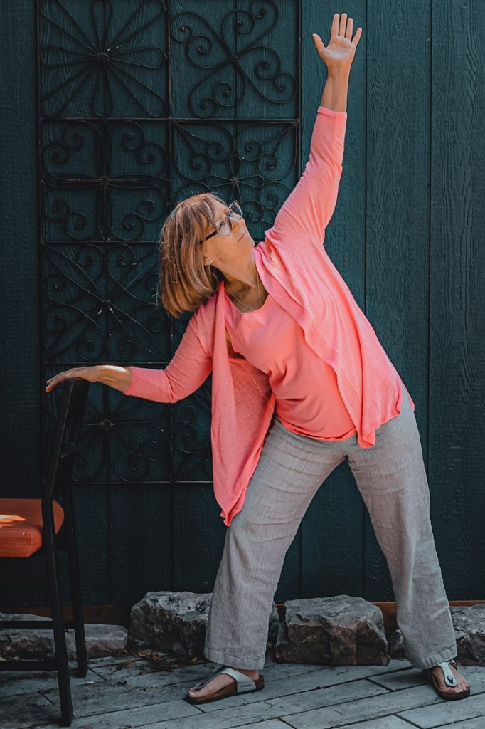 Heather Skoll performing warrior pose with chair support